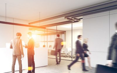 82057396 - business people in suits are walking in a modern office lobby with glass and white walls, a concrete floor and a white reception counter. 3d rendering mock up toned image